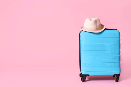 Modern blue suitcase and hat on light pink background. Space for text