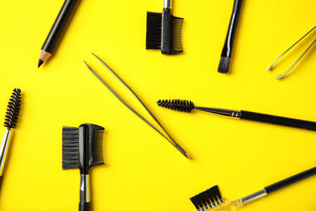 Set of professional eyebrow tools on yellow background, flat lay Stock Photo