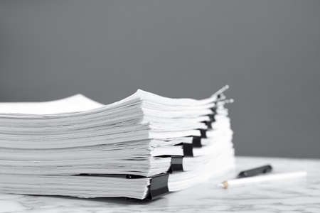 Stack of documents with binder clips on marble table against grey background
