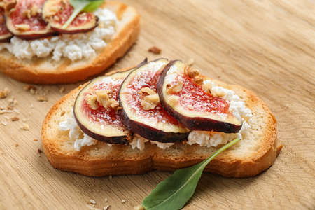 Bruschettas with cheese and figs on wooden board, closeup