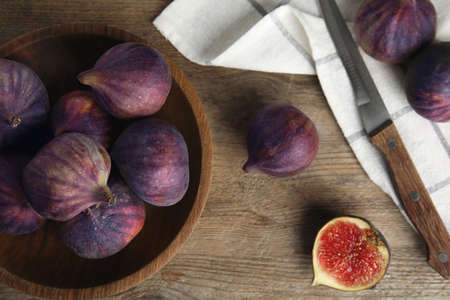 Bowl with ripe figs on wooden table, flat lay