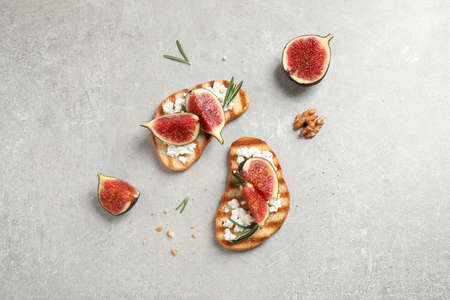 Bruschettas with ripe figs and cheese on light table, flat lay Reklamní fotografie