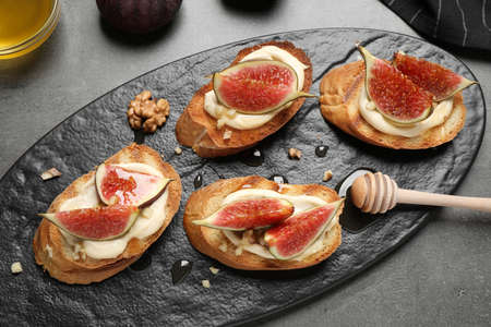 Bruschettas with ripe figs and cream cheese served on grey table, top view Reklamní fotografie