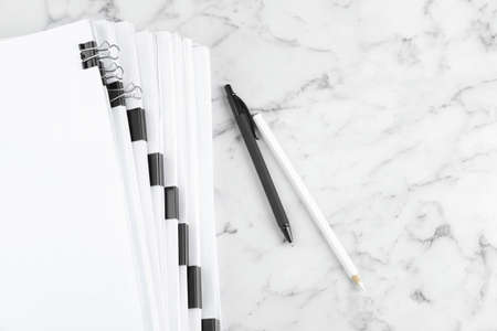Stack of documents with binder clips on marble table, top view