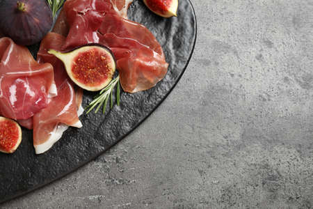 Delicious ripe figs and prosciutto served on grey table, top view. Space for text Reklamní fotografie
