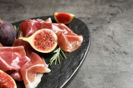 Delicious ripe figs and prosciutto served on table