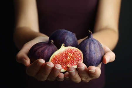 Young woman with handful of tasty ripe figs on black background, closeup Stock Photo
