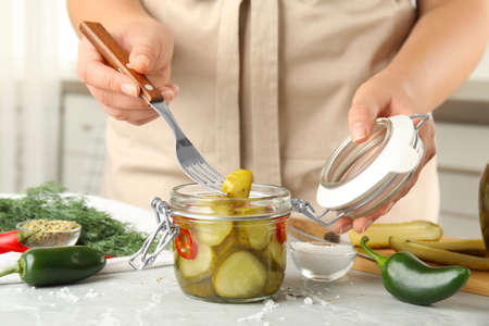 Woman taking pickled cucumber from jar at table in kitchen, closeup view Stockfoto