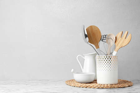 Different kitchen utensils on table against light background. Space for text