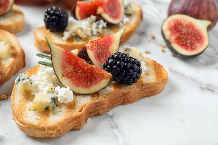 Bruschettas with cheese, figs and blackberries served on white table, closeup Stockfoto