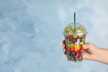 Woman holding plastic cup with fresh tasty fruit salad against light blue background, closeup. Space for text