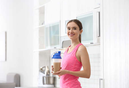 Athletic young woman with protein shake in kitchen