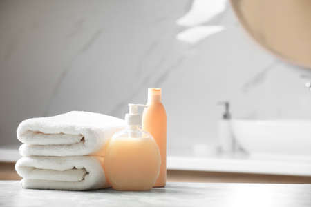 Folded towels and toiletries on marble table in bathroom, space for text Reklamní fotografie