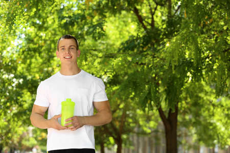 Athletic young man with protein shake at green park Imagens