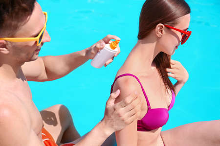Young man applying sun protection cream onto girlfriend at swimming pool 스톡 콘텐츠 - 129979861