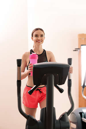 Athletic young woman with protein shake on running machine in gym