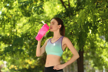 Athletic young woman drinking protein shake at green park
