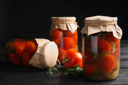 Pickled tomatoes in glass jars on black wooden table
