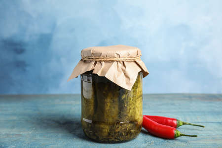 Jar with pickled cucumbers on wooden table against blue background