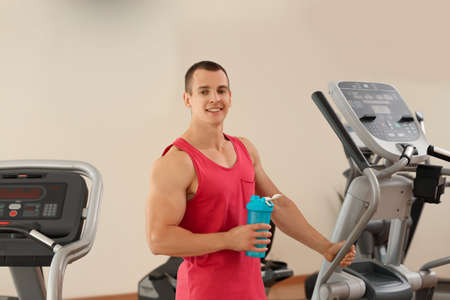 Athletic young man with protein shake on running machine in gym Imagens