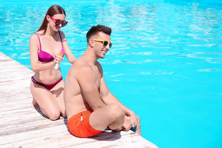 Young woman applying sun protection cream onto boyfriend at swimming pool