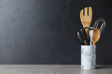 Holder with kitchen utensils on table against dark background. Space for text