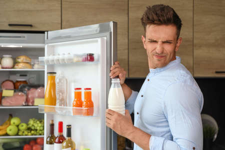 Man taking bottle with old milk out of refrigerator in kitchen