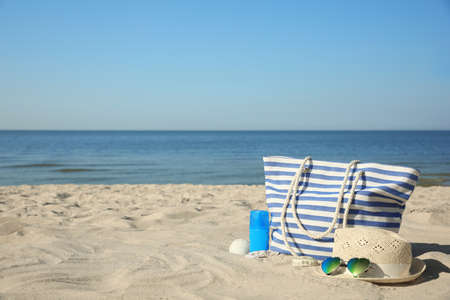 Stylish beach accessories on sandy sea shore Reklamní fotografie