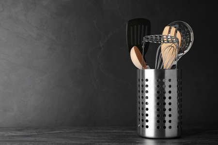 Holder with kitchen utensils on grey table against dark background. Space for text Stock Photo