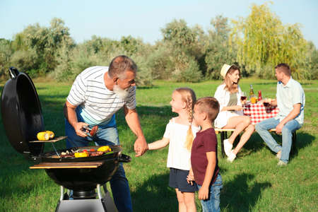 Grandfather with little kids cooking food on barbecue grill and their family in park Stockfoto
