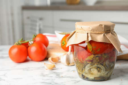 Pickled tomatoes in glass jar and products on white marble table in kitchen
