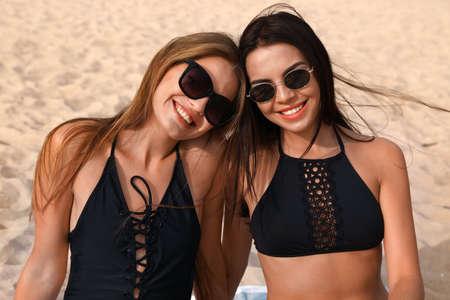 Jeune femme en bikini avec petite amie sur la plage. Beau couple