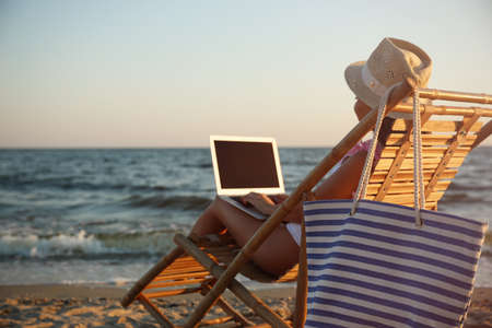 Young woman with laptop in deck chair on beach