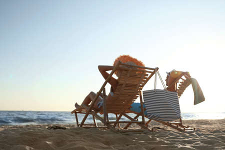 Young couple relaxing in deck chairs on beach near sea Stock fotó