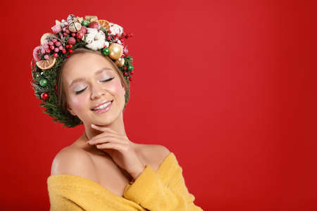 Beautiful young woman wearing Christmas wreath on red background. Space for text