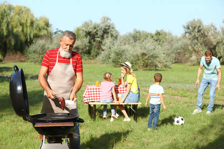 Happy senior man with meat at barbecue grill and his family having picnic in park