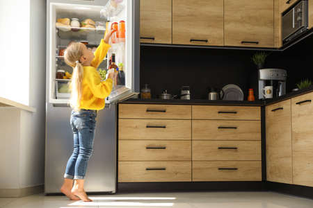 Girl taking bottle with juice out of refrigerator in kitchen
