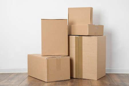 Pile de boîtes en carton près du mur blanc à l'intérieur
