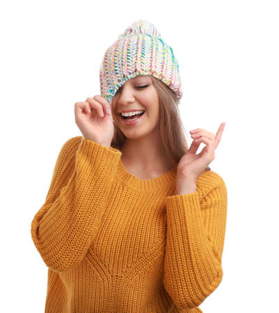 Funny young woman in warm sweater and hat on white background. Winter season