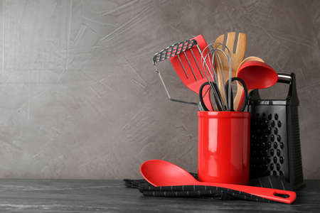 Holder with kitchen utensils on grey table against grey stone background. Space for text Stock fotó
