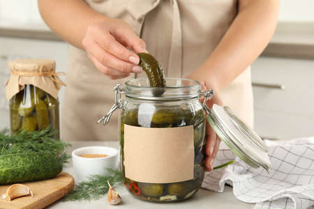 Woman taking pickled cucumber from jar at table in kitchen, closeup view. Space for text Stock Photo