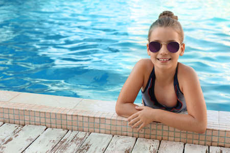 Happy little girl with sunglasses in swimming pool on sunny day