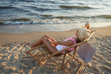Young woman relaxing in deck chair on beach
