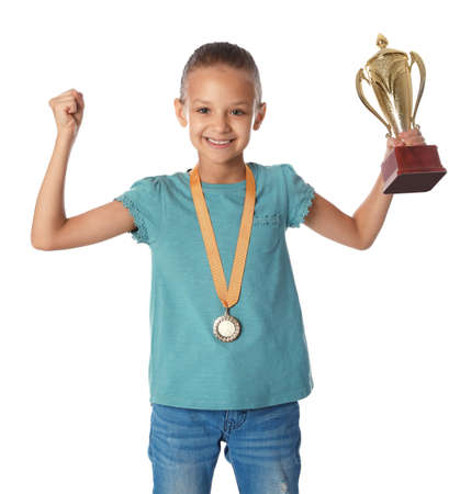 Happy girl with golden winning cup and medal on white background