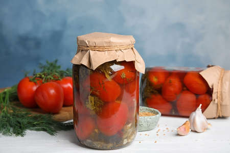 Pickled tomatoes in glass jars and products on white wooden table against blue background