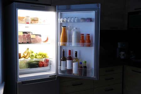 Öffnen Sie nachts den Kühlschrank voller Produkte in der Küche