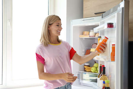 Woman with bottle of juice near open refrigerator in kitchen