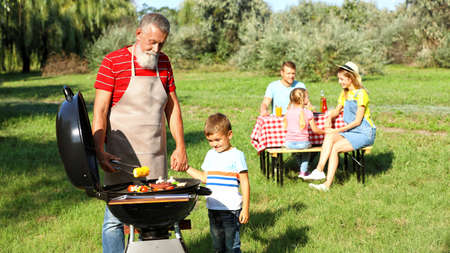 Grandfather with little boy at barbecue grill and their family in park 版權商用圖片