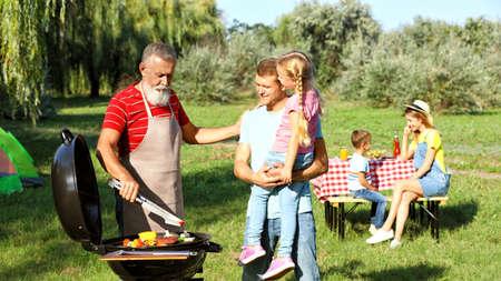 Happy family having barbecue in park on sunny day 版權商用圖片