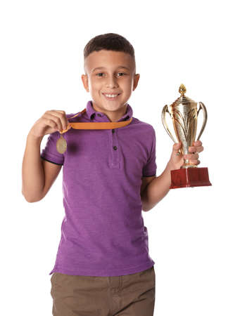 Happy boy with golden winning cup and medal on white background
